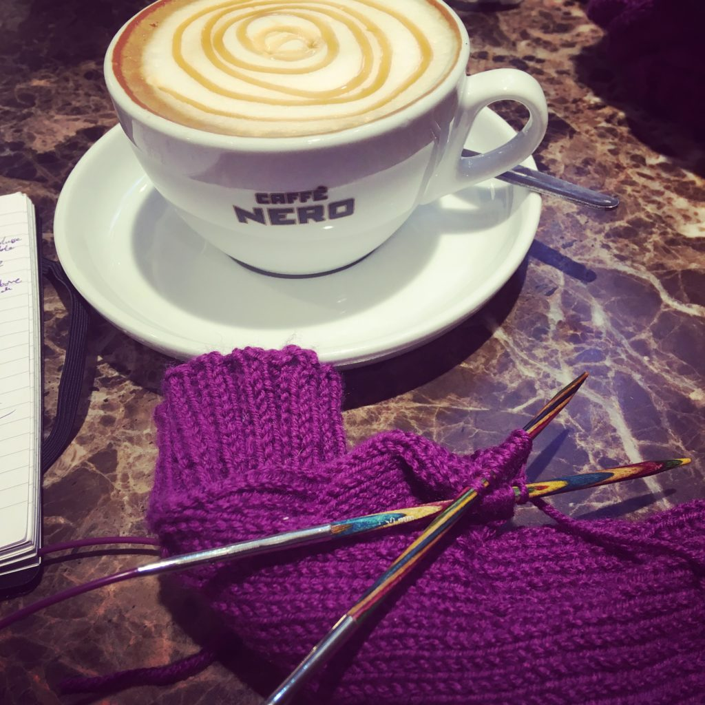 In the foreground there is a purple mitten with knitting needles through part of them. There is a coffee cup in the background