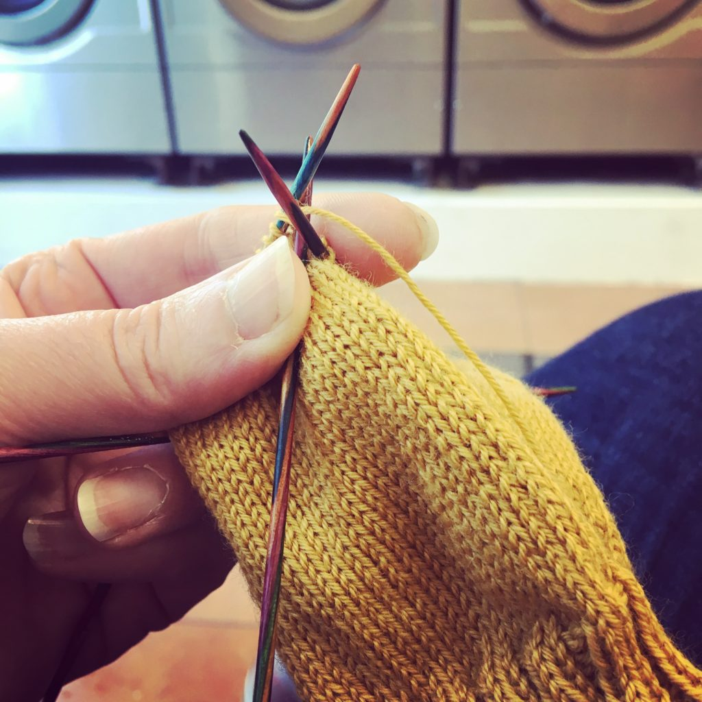 Hand holding some mustard yellow knitting on double-point needles. There's a row of washing machines in the background.
