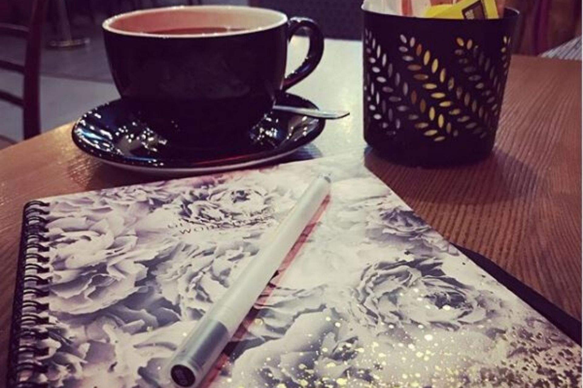 essential writing tools: a notepad, a pen and coffee