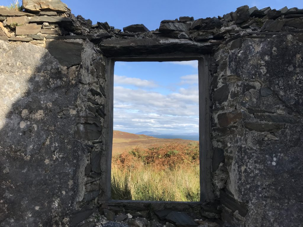an empty window framing the sea. The frame is in a wall that has no roof above it.