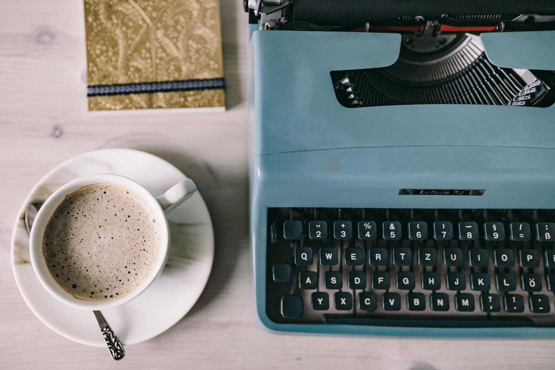 image of old portable typewriter with a cup of coffee and a notebook